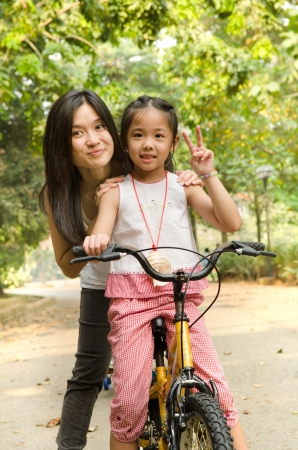 chinese mother having good time on bicycle with her daughter outdoor, peace sign photo