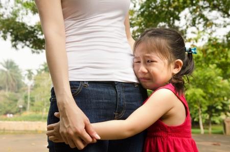 bambini tristi: bambina asiatica piange e abbraccia la sua madre Archivio Fotografico