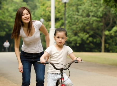 chinese mother teaching her daughter riding bicycle outdoor photo