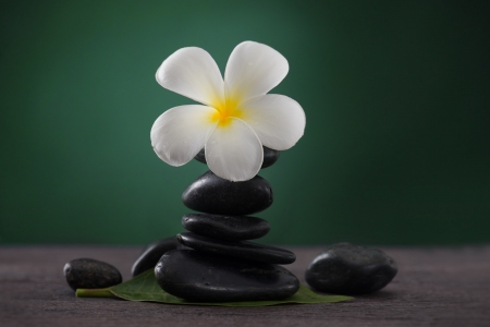 a serene life: Stacked hot stones for massage spa and frangipani with green background   Stock Photo