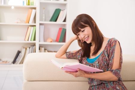 casua: Asian girl reading a book in livingroom