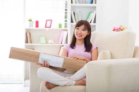 asian chinese woman receiving an online shopping package delivery from a courier at her home.   photo