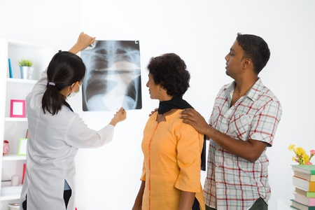 family doctor: indian family senior female doing medical x-ray scan with asian doctor