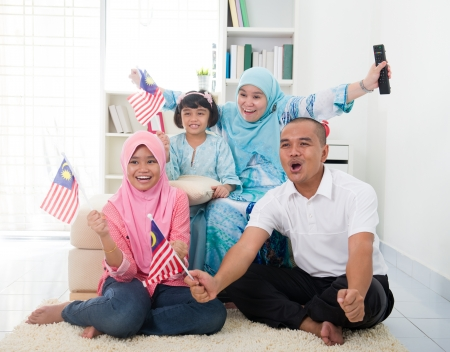 malaysian family celebrating while watching television over a tournament , some are carrying country flags photo