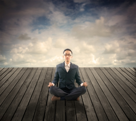 photos of business man relaxation on outdoor wood plank platform , lotus yoga stance photo