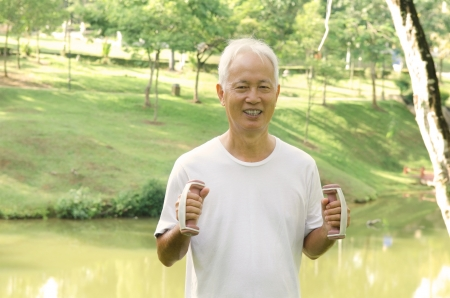 chinese Asian senior man healthy lifestyle working out on a park with a dumbbell photo