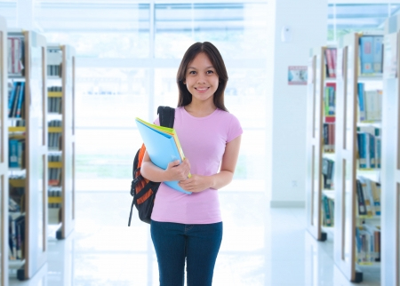 Portrait of friendly asian hispanic looking female college student looking at someone in the library photo