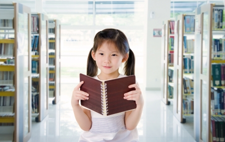 uniform skirt: smart looking little chinese school girl read at the library
