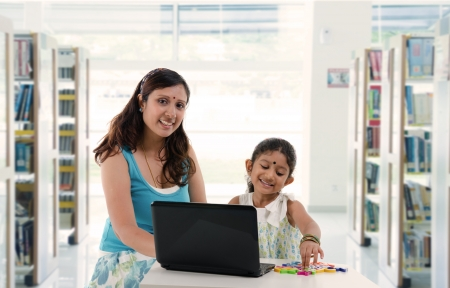 south asian: mother and daughter with laptop learning inside a library, indian south asian people