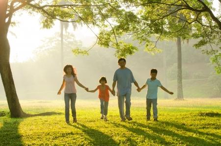 famiglia in giardino: famiglia all'aperto godendo tempo qualitye insieme, le persone asiatiche silhouette durante bellissima alba