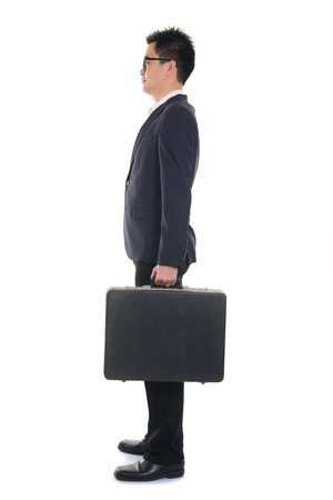 asian business male standing and holding a suitcase ,full body side view isolated on white background , chinese man photo