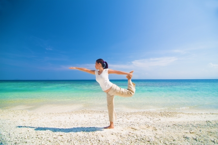 beach yoga performed by a matured asian female photo
