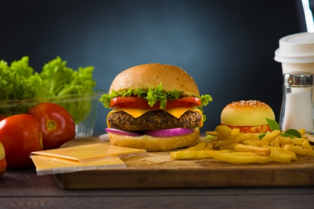 charbroiled: cheese burger with plenty of fast foods ingredients on the background