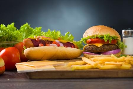 perro caliente: hamburguesa con queso y salchichas con un mont�n de comida r�pida ingredientes en segundo plano