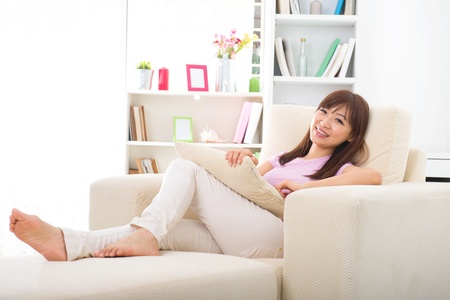 Beautiful smiling Asian woman with tablet computer. Lying on sofa