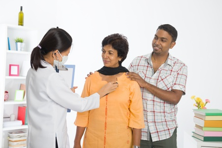 old man on a physical pressure: indian punjabi senior medical checkup with an asian female doctor