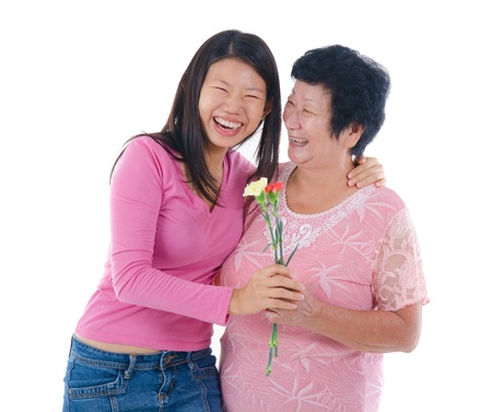 ageing: Happy Asian Chinese Mother and Daughter with carnation flower with isolated white background