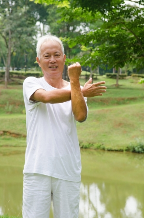 Retired Asian chinese senior man exercising in park     photo