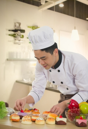 garnishing: asian chinese chef preparing foods for his customer with kitchen background Stock Photo