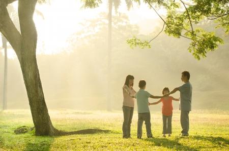 Glückliche asiatische Familie mit Zeit beim Spielen im Freien grünen Park in einem wunderschönen Sonnenaufgang