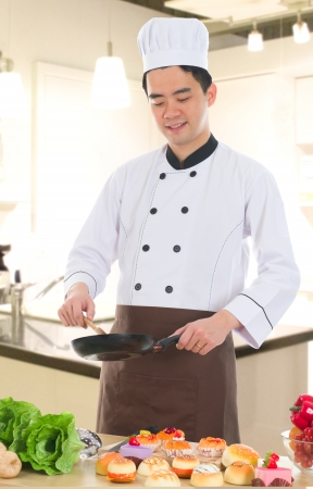 asian chinese chef preparing foods for his customer with kitchen background photo