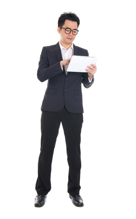 asian business male using tablet on isolated white background, full length photo
