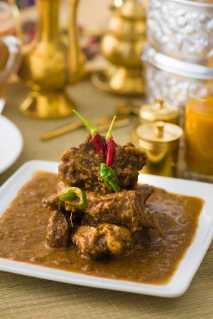 lamb korma famous food with traditional indian background items photo