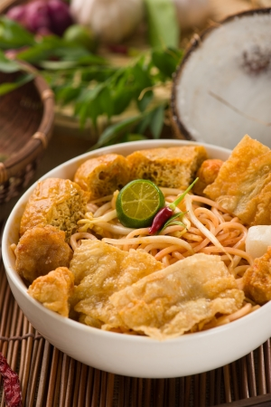 laksa: curry noodle malaysian penang style with raw ingredients on background