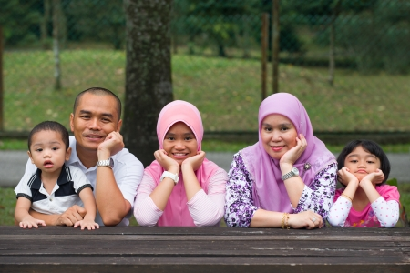 Happy Malay Asian Family enjoying family time together in the park