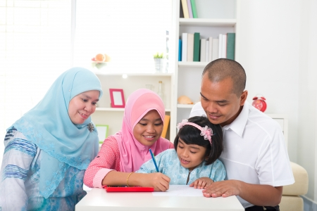 learning by doing: indonesian family learning together doing home work with lifestyle background   Stock Photo