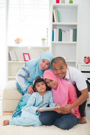 malay family using tablet having a good time surfing internet   photo