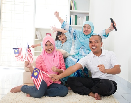malaysian family celebrating while watching television over a tournament , some are carrying country flags