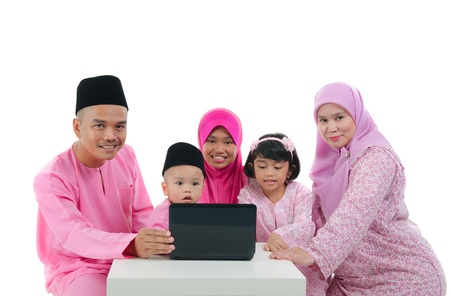 malay family with traditional maalysian traditional clothes and learning computer   photo