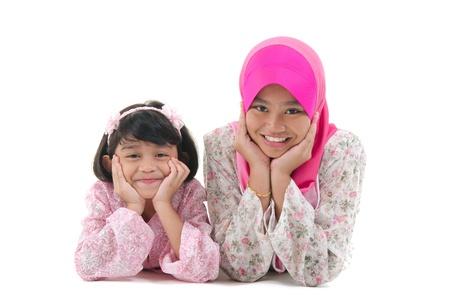 petite fille musulmane: s?urs malais pose sur le sol avec un fond blanc isolé Banque d'images