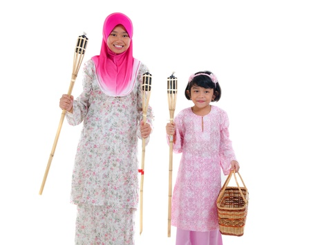 malay sisters with oil lamp during hari raya festival photo