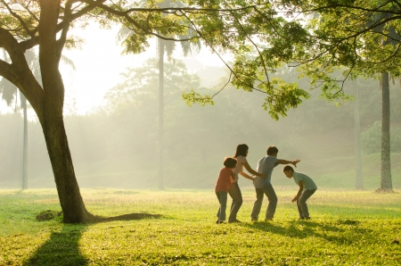 an asian family having fun playing in the park early morning   Stock Photo