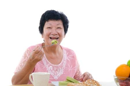 ready to eat: chinese senior female eating with isolated white background