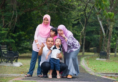 family time: Happy indonesian Family enjoying family time together in the park   Stock Photo