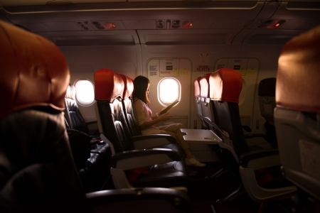 seating: Interior of airplane with passenger reading on seats during a sunset, lowlight ambience mode