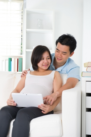 Husband and pregnant wife using tablet computer sitting on sofa at home photo