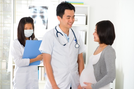 asian doctor performing pregnancy medical check up   photo