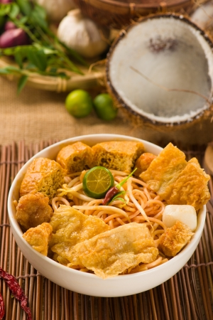 laksa: singapore laksa curry noodles with plenty of raw ingredients as background