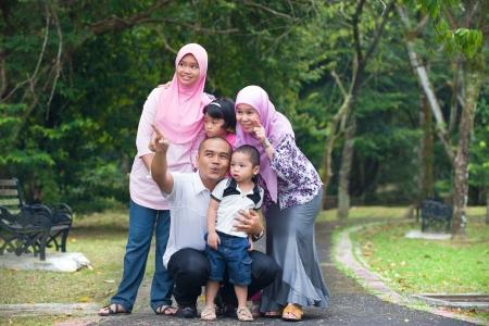 petite fille musulmane: Happy Family indon?sienne profiter du temps en famille dans le parc Banque d'images
