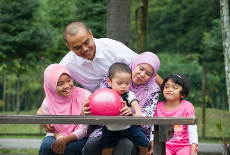 malay muslim family having fun in the park Stock Photo