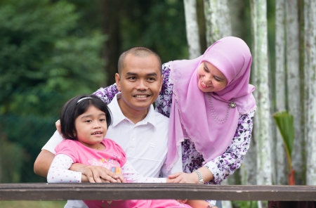 malay muslim family having fun in the park photo