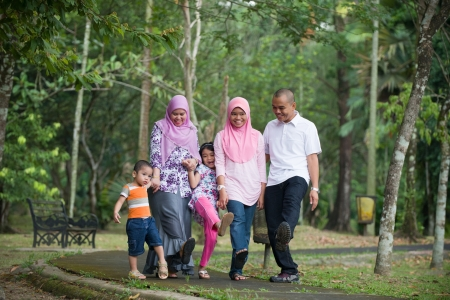 Happy indonesian Family enjoying family time playing together in the park   photo