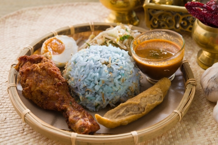 Traditional Malaysian food. Nasi kerabu is a type of nasi ulam, popular Malay rice dish. Blue color of rice resulting from the petals of butterfly-pea flowers. Asian cuisine.   Stock Photo