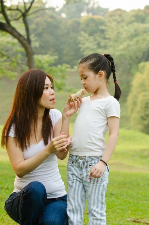 asian chinese girl feeding her mother in outdoor green park   photo