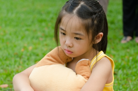 depressed Asian chinese child. Little girl showing her unhappy face at outdoor