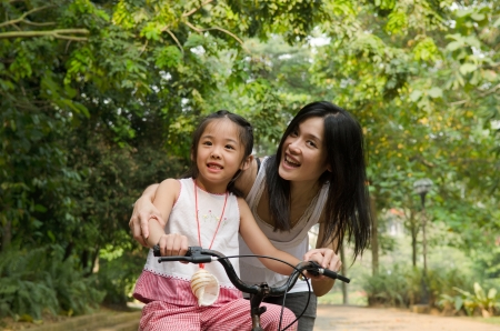 asian chinese mother teaching her daughter riding bicycle outdoor Stock Photo